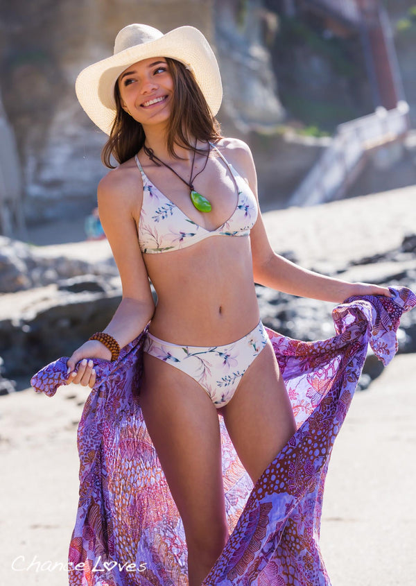 Young woman wearing a cowboy hat at the beach, in an amazing looking floral bikini.