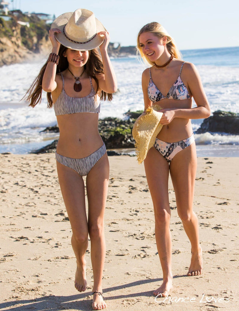 Aria and Chance Colette are walking on the beach, both wearing the Reversible Isla Bikini.