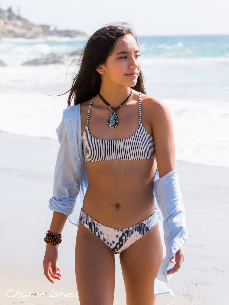 Beautiful young woman walking on the beach in her bikini designed by Chance.