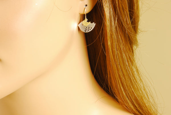 a model wearing mother bird earrings
