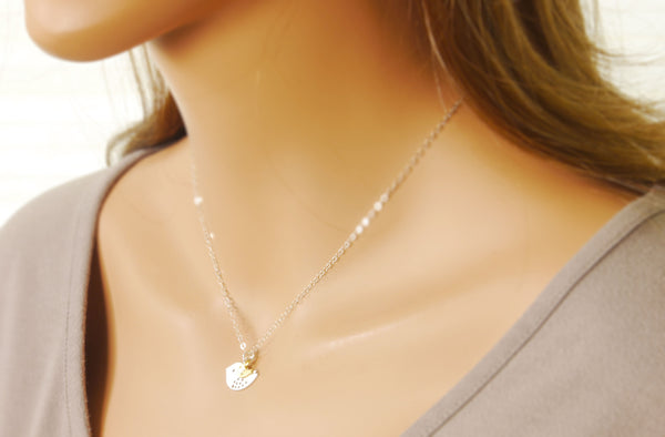 a model wearing the baby bird necklace