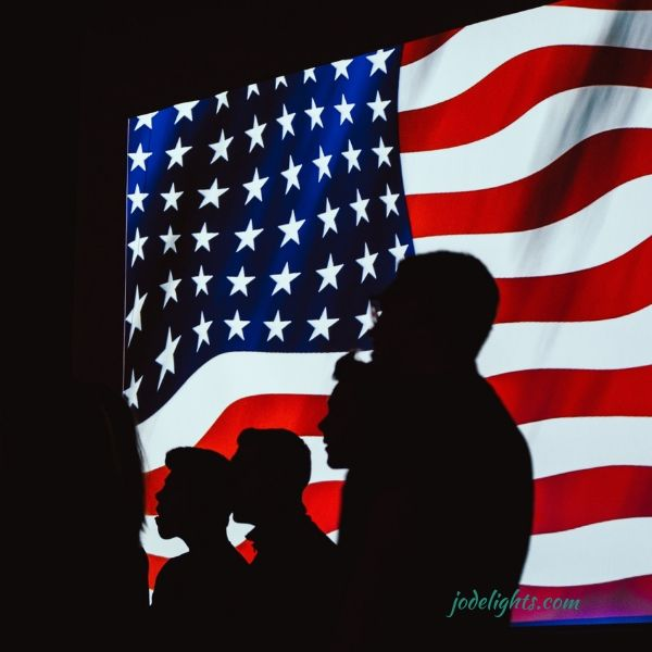 men in silhouette in front of US Flag