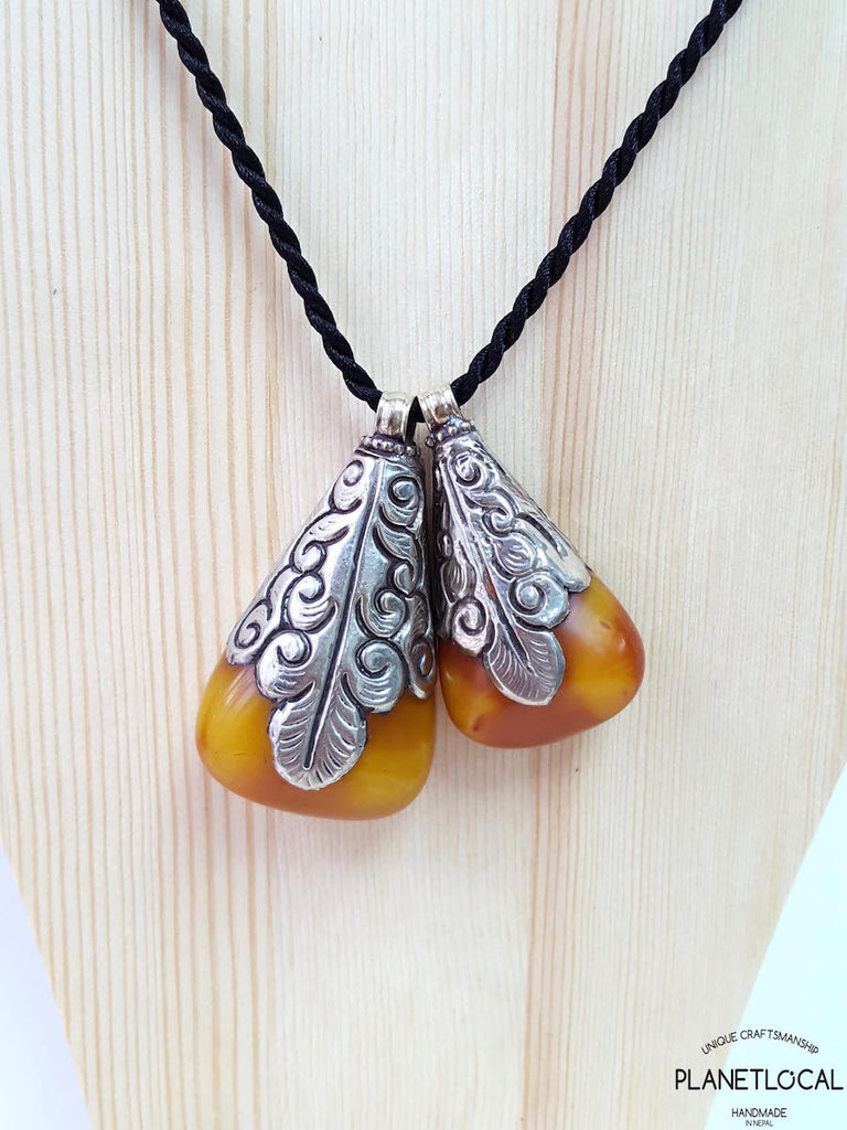 Resin Amber Pendant wrapped with traditional Tibetan white metal carvings
