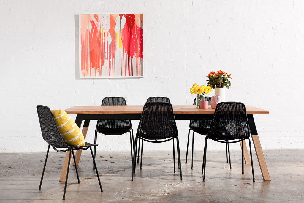 Luxe industrial styled square leg dining table pictured with pink abstract painting.