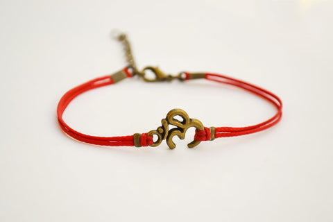Red bracelet with bronze tone Om charm - shani-adi-jewerly