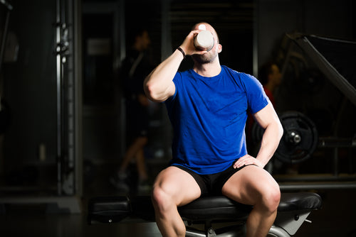 man in gym drinking protein powder