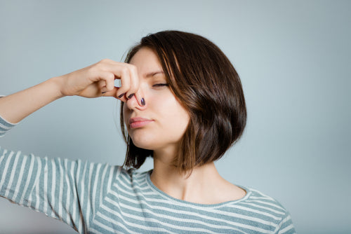 woman pinching nose due to bad odor