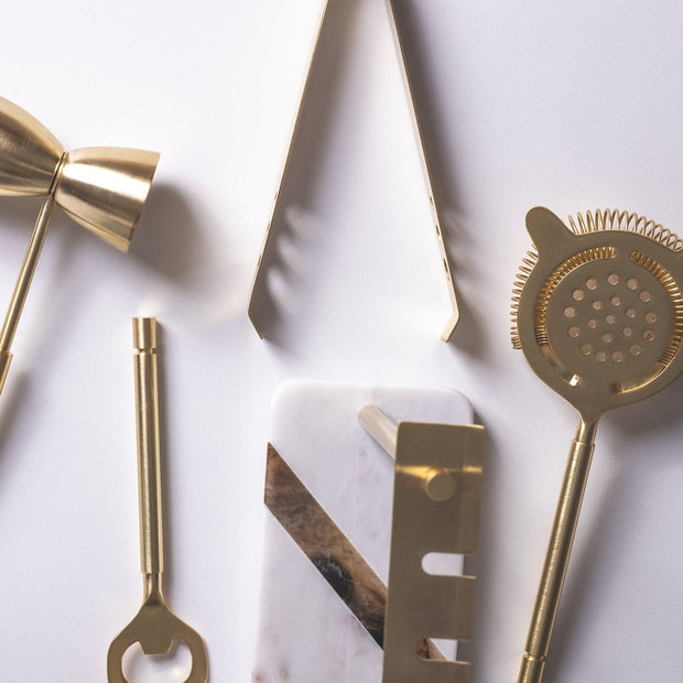 Gold cocktail strainer, gold cocktail bottle opener and jigger