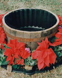 Wooden barrel-style pot surrounded by red flowers and protected by the flex-o-liner barrier.