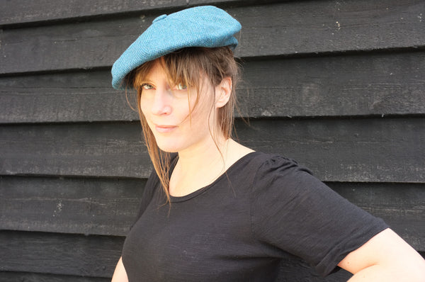 Girl in a Blue Sussex Tweed 'Brighton' cap standing next to a fishermans hut in Hastings.