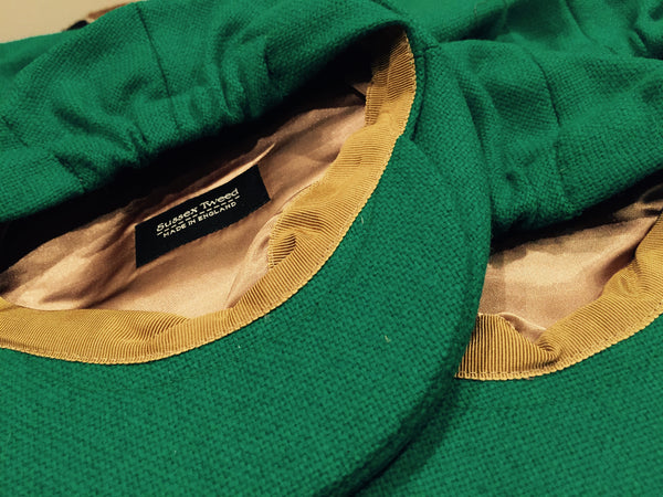 Two Sussex tweed Kids' caps, lying on top of each other, in green tweed, with gold satin linings, and a gold coloured grosgrain sweatband.