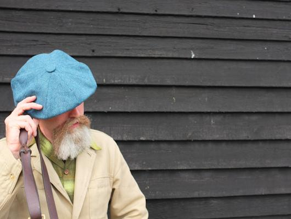 Bearded man adjusts his blue Sussex Tweed 'Brighton' cap standing in front of a net drying shed in Hastings.