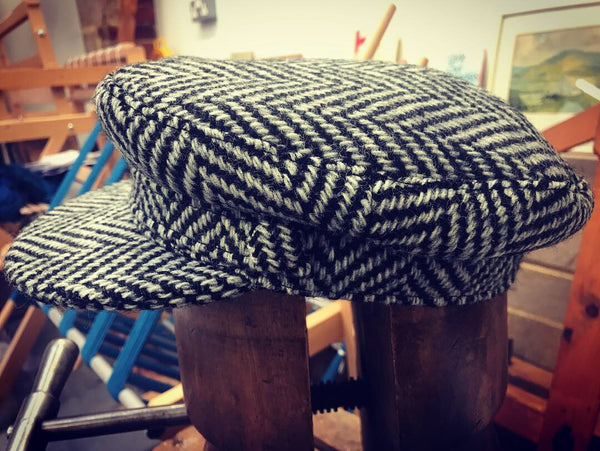 A side view of the Sussex Tweed 'Rock-a-Nore' fisherman's peaked cap, in a light grey herringbone, handwoven tweed, displayed on a hat stretcher, in front of some looms.
