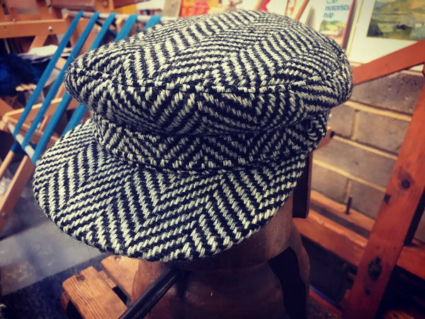 A Sussex Tweed 'Rock-a-Nore' fisherman's peaked cap, in a light grey herringbone, handwoven tweed, displayed on a hat stretcher, in front of some looms.