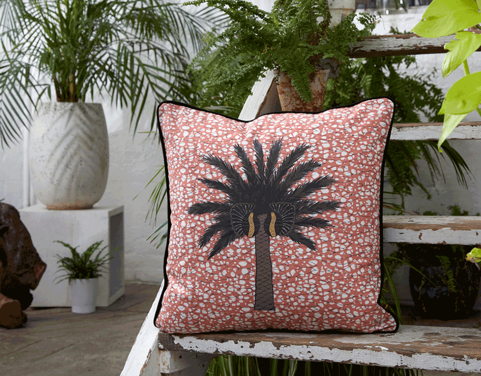 Colourful copper pink African batik print cushion with large tropical palm tree