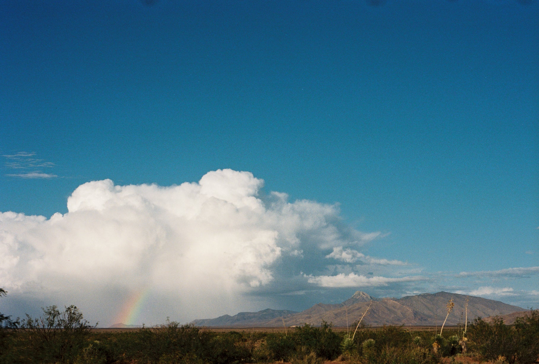 A rainbow over a desert landscape with mountains and white clouds in the foreground and a blue sky above. Photo by Krysta Jabczenski.