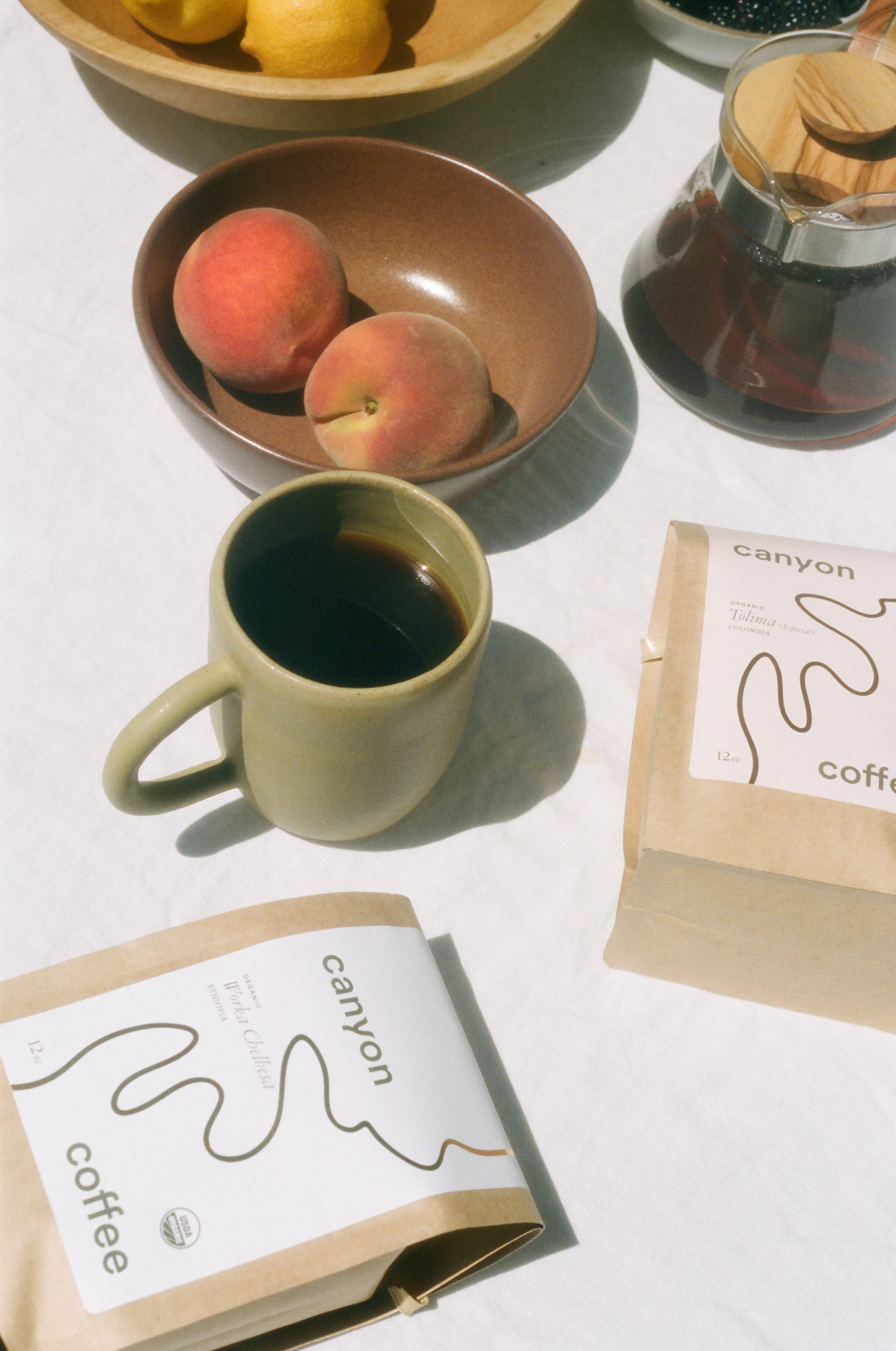 Bags of Canyon Coffee on a table with fruit and ceramic mug.