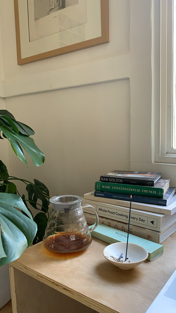 Glass coffee server and Bodha incense holder on a desk near a plant in the home of Canyon Coffee founders Ally Walsh and Casey Wojtalewicz