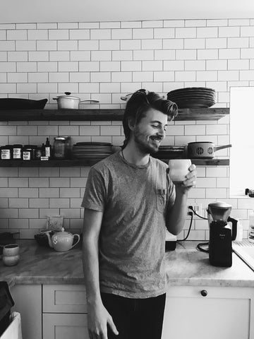 Black and white photo of Casey Wojtalewicz, founder of Canyon Coffee, drinking a coffee tonic by Lacy Phillips, founder of Free + Native, in Lacy's Echo Park home