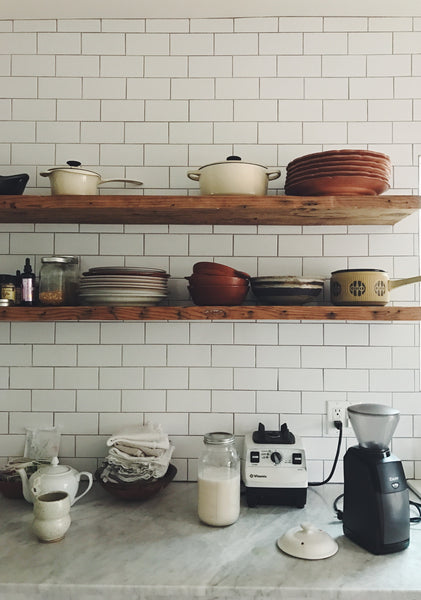 Lacy Phillips' white-tile kitchen in Los Angeles, with wooden shelves, ceramic bowls, a vitamin and burr grinder.