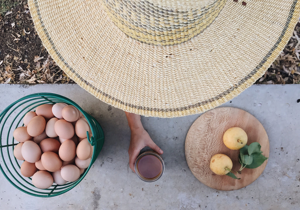 An overhead shot of fresh eggs from Full Belly farm, a straw hat, iced coffee and lemons