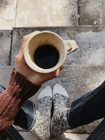 Girl holding cup of coffee on sidewalk | Canyon Coffee