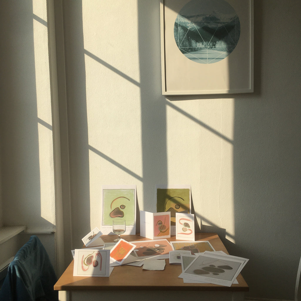 Art prints on a table in France, by Arianna Jones