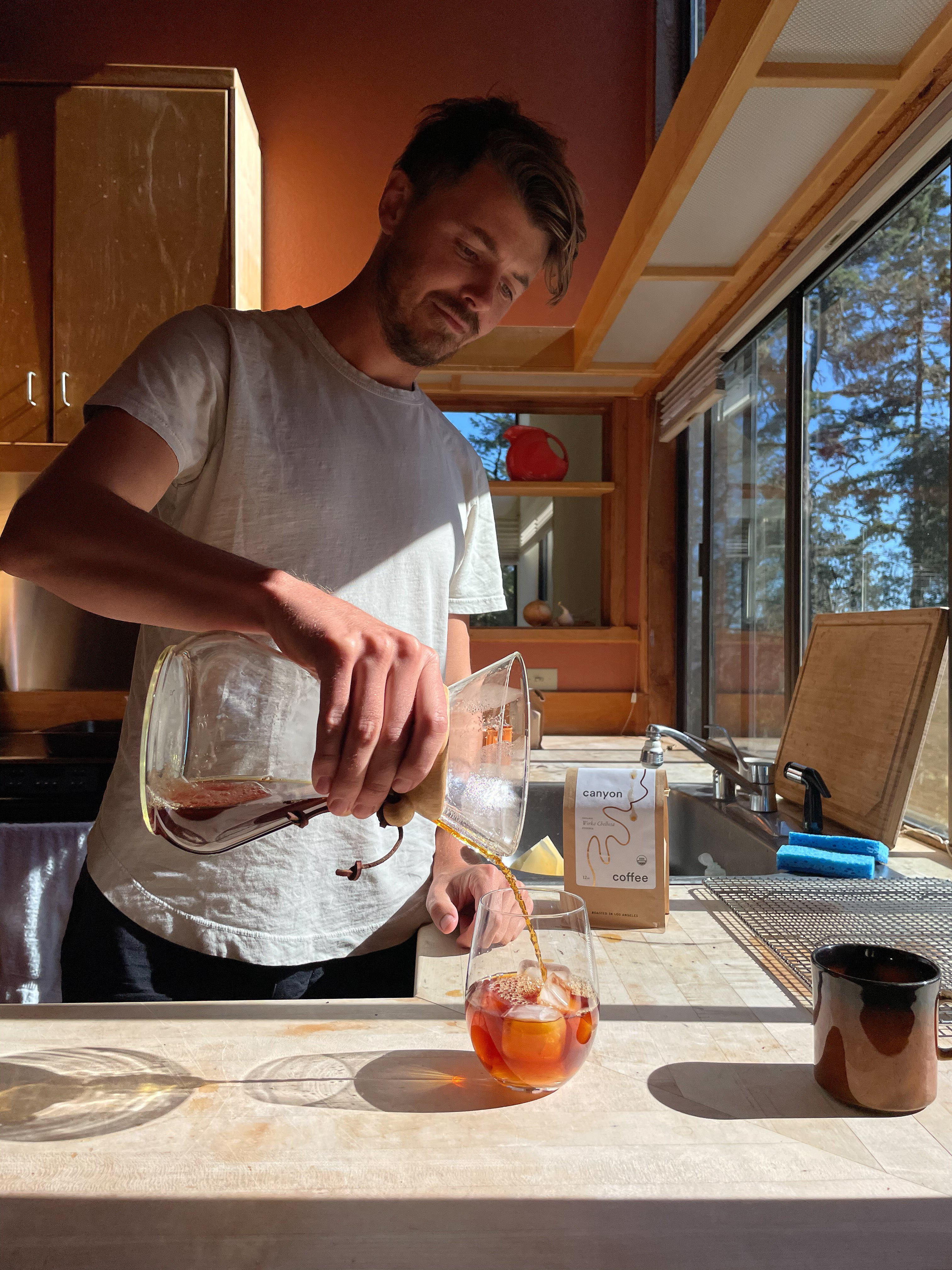 Casey Wojtalewicz pouring iced coffee from a Chemex into a tumbler with ice in a bright, sunny cabin in Sea Ranch, California.