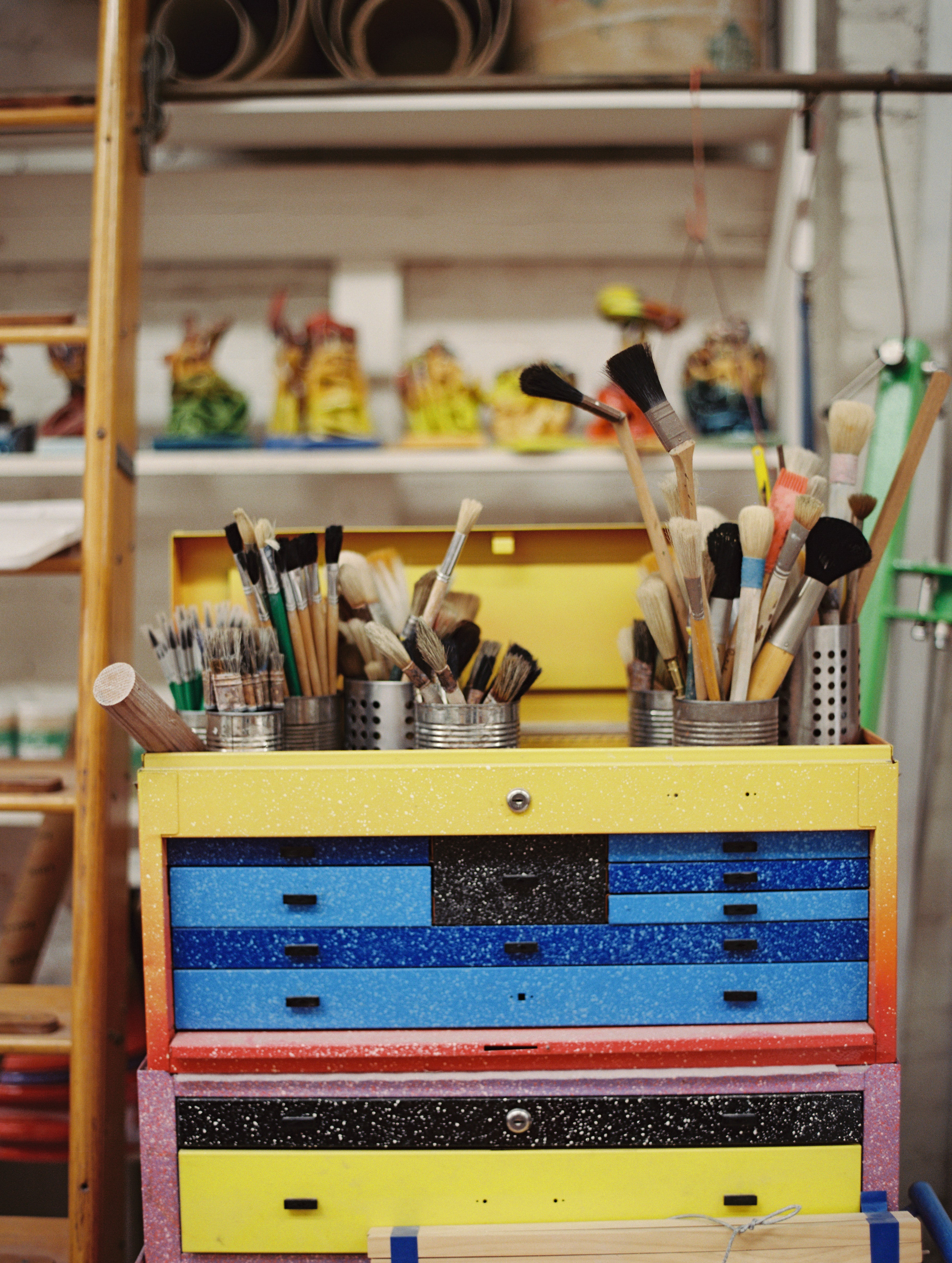 Multiple cans of paintbrushes on a colorful artist flat file box in the studio of Peter Shire. Photo by Justin Chung.
