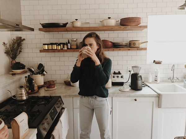 Lacy Phillips, founder of Free + Native, drinking tea in her white tile kitchen in Los Angeles, California