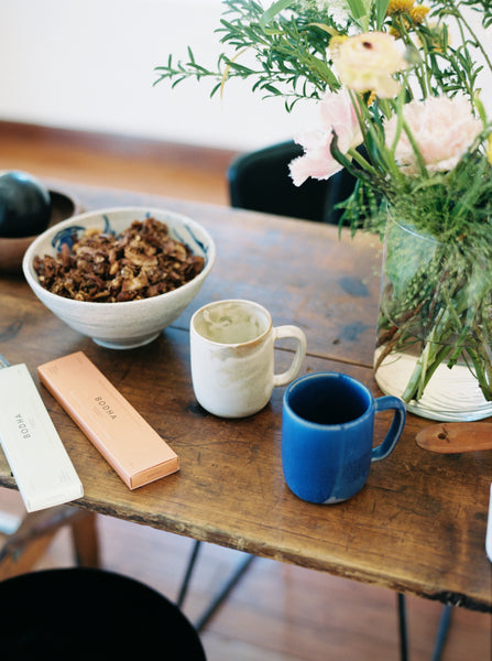 Kitchen table with two packages of Bodha smokeless incense, a bowl of granola, and a white and blue ceramic mugs by Luvhaus for Canyon Coffee. Photo by Justin Chung.