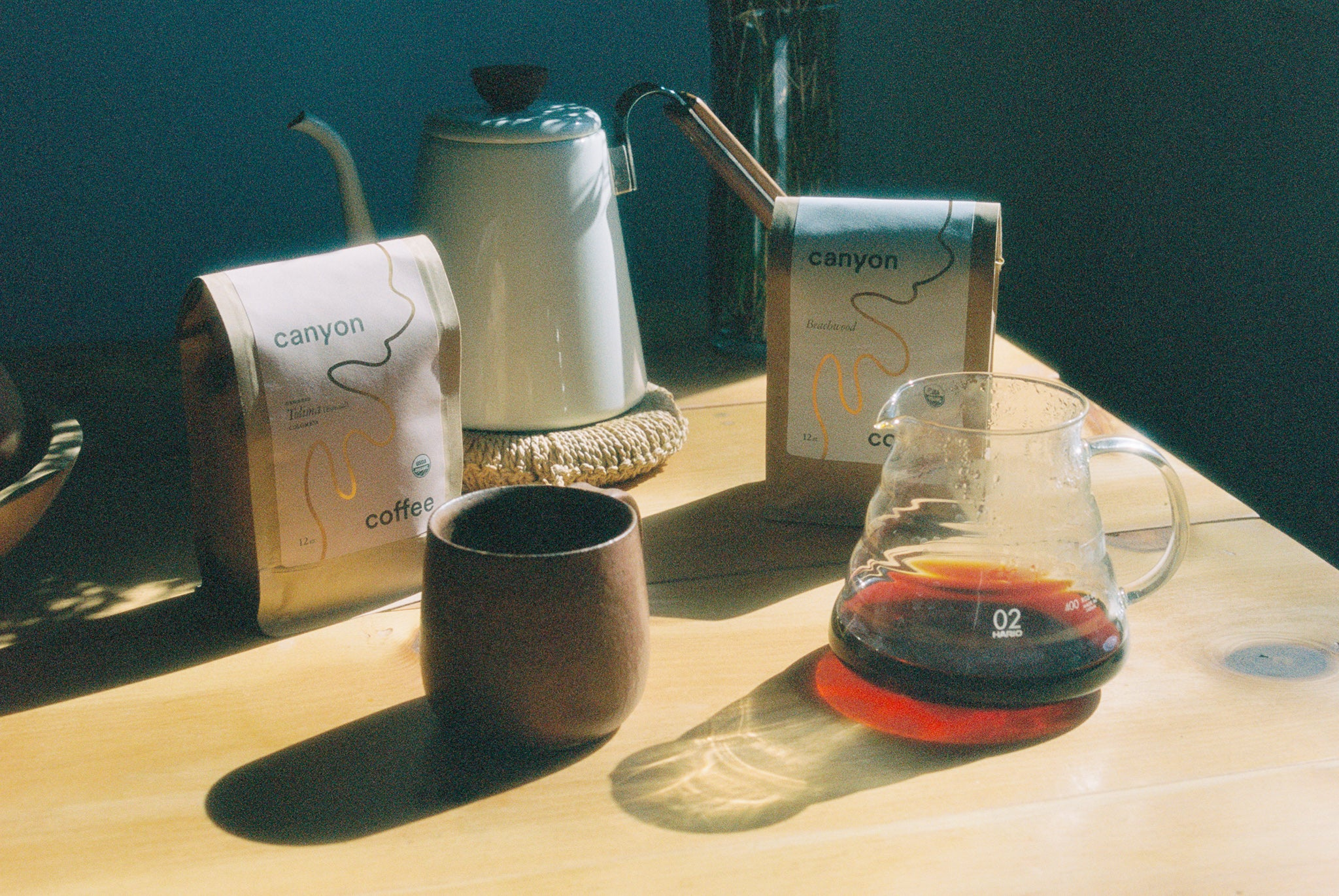 Canyon Coffee on a kitchen table: bag of Canyon Coffee, mug by Alison Andersson, and V60 with black drip coffee