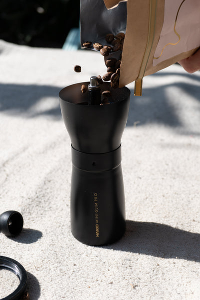 Pouring a bag of Canyon Coffee beans into a ceramic mill hand grinder by Hario