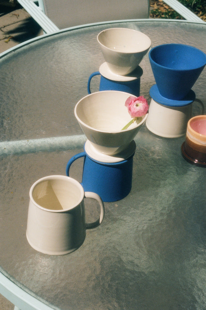 White and blue ceramic coffee drippers and mugs by Zizi Ceramics. Photo by Drew Escriva.