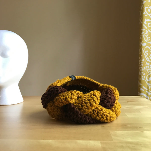 Brown and Yellow, Crocheted headband, braided headband, crocheted ear warmer, braided ear warmer, mustard yellow and chocolate brown, on table front view