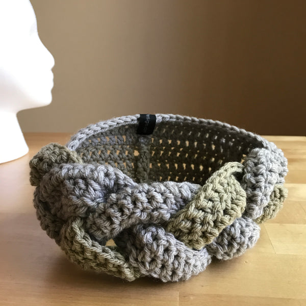 Tan and Gray braided headband, crocheted headband, braided headband, braided ear warmer, on table front view