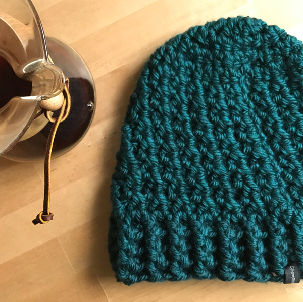 Peacock blue slouchy beanie hat on table