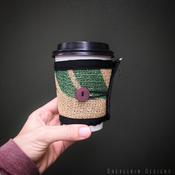 Coffee Cozy for travel or disposable cups with purple button and green leaves in hand