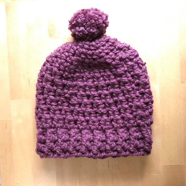 Purple Wool Slouchy Beanie with Pom Pom on table front