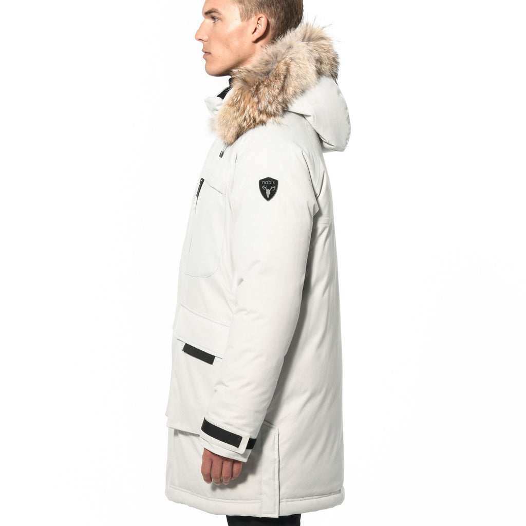 Men's thigh length down-filled parka with removable hood and removable coyote fur trim in Chalk | color
