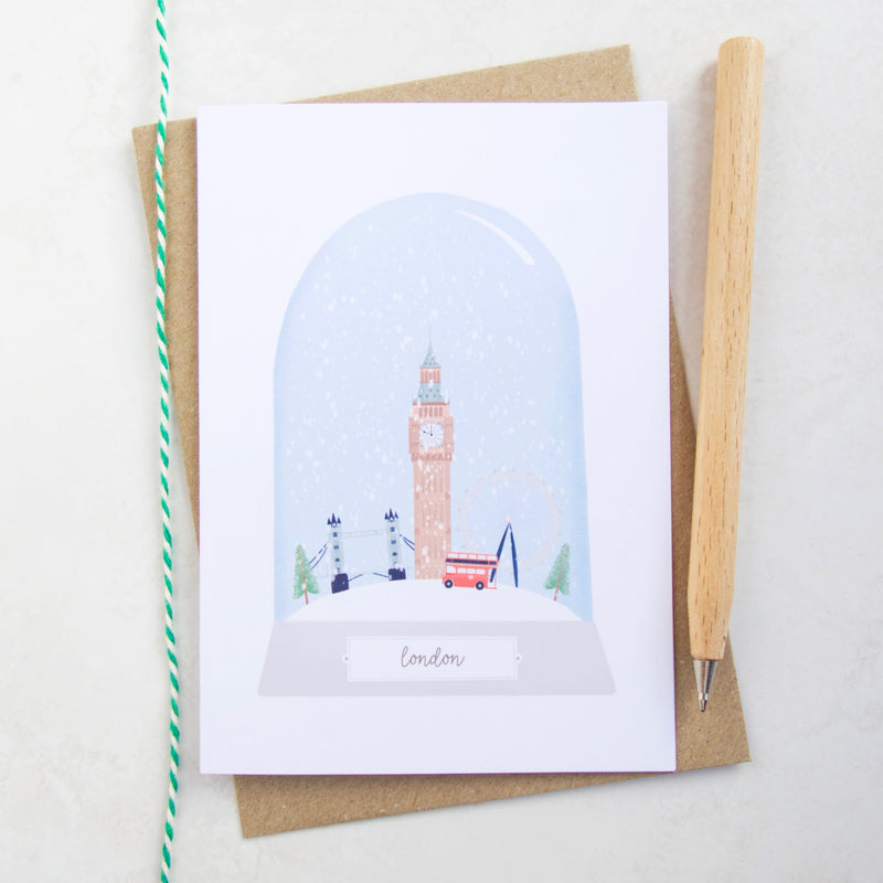 An illustrated Christmas card featuring the city of London in a snow globe.