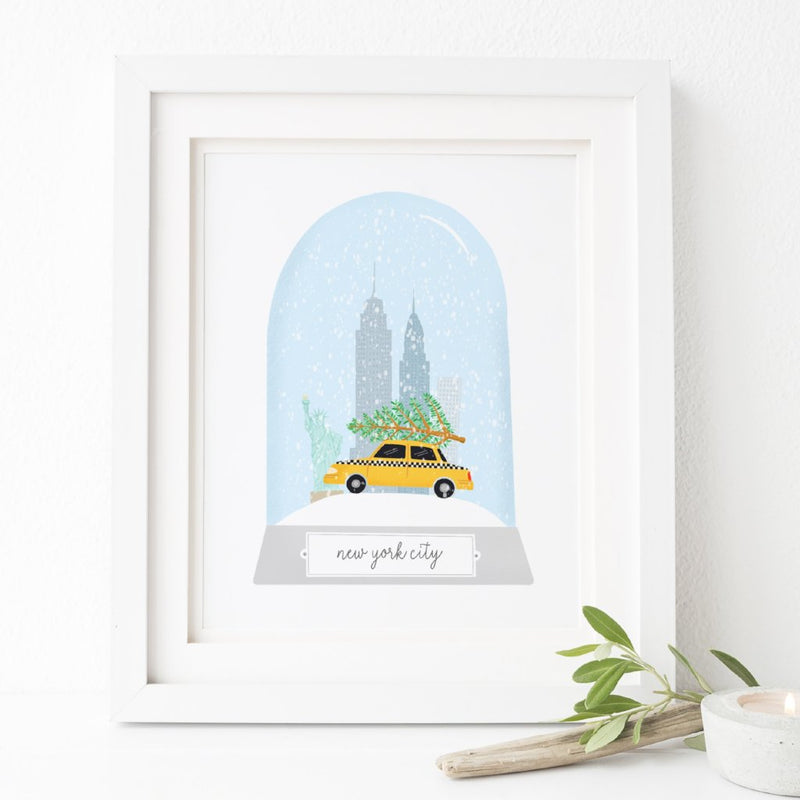 An illustrated New York City Christmas print featuring illustrations of some of NYC's most famous landmarks in a snow globe.