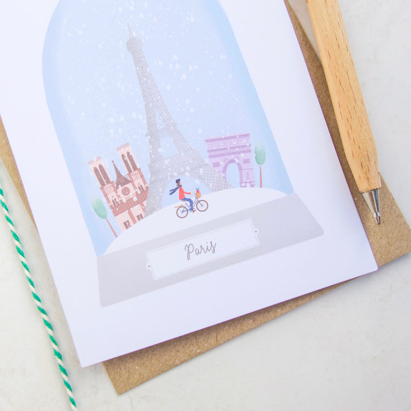 A close up image of the snow globe illustration on the Paris Christmas card.