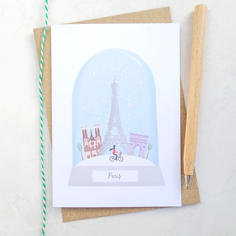 An illustrated Christmas card featuring the city of Paris in a snow globe.