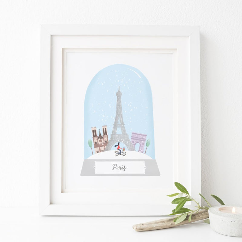 An illustrated art print of Paris at Christmas featuring the city's most famous landmarks inside a snow globe.