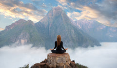 Girl sat on a rock meditating in the mountains