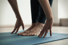 Hands and feet on blue yoga mat