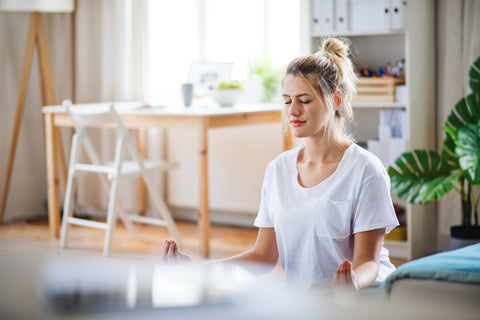 Woman in a white t shirt meditating at home