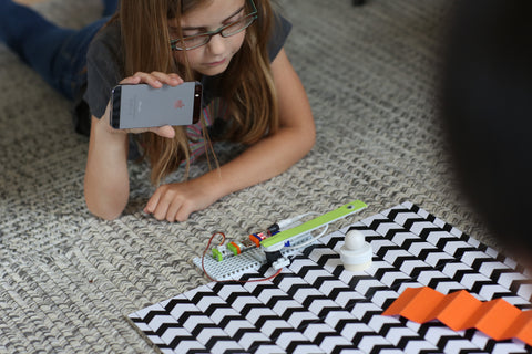 Girl on carpet holding phone over her littleBits invention.