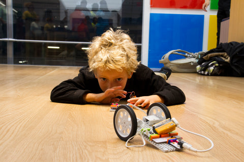 Kid laying on the floor controlling his robot car invention.